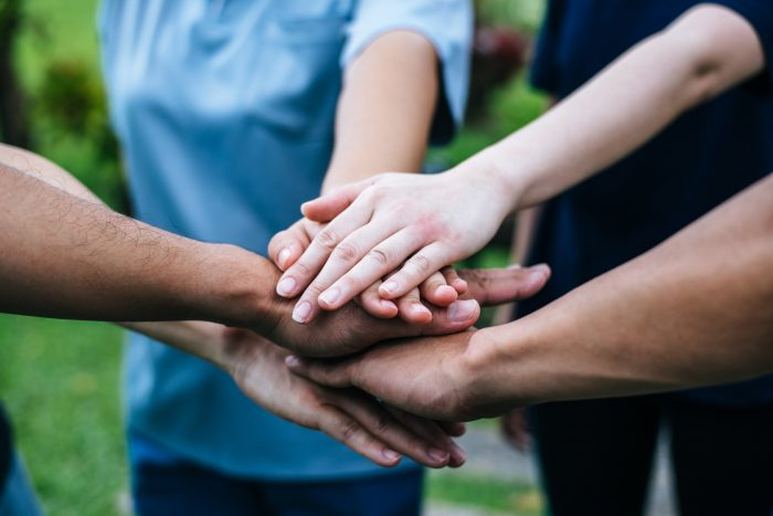 polyglots of different ethnicities stacking hands together